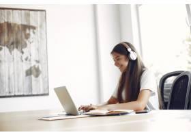 年轻的学生坐在桌子旁使用笔记本电脑_5913132