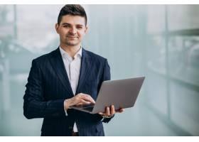 年轻英俊的商人在办公室里拿着笔记本电脑_7435592