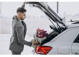 年轻英俊的商人送来一束美丽的鲜花_7377604