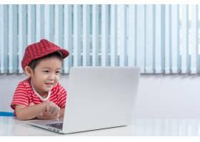 可爱的男孩在儿童房里玩笔记本电脑_1285554