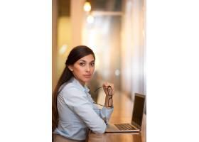 在咖啡馆里用笔记本电脑工作的严肃迷人的女_992948