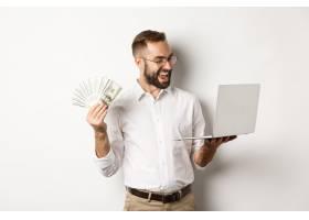 商务和电子商务满意的商人拿着钱在笔记本_11651732