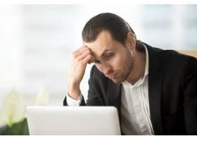 困惑的年轻商人看着笔记本电脑屏幕_4013318