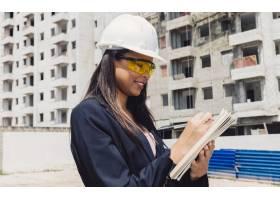 在在建建筑附近戴着安全帽带记事本的非洲_3724289