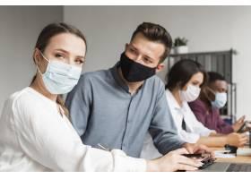 在大流行期间办公室里的人戴着口罩一起工_10070469
