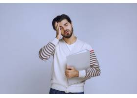一名男子完成了项目拿着文件夹疲惫的样_13406741