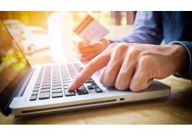 一名男子手里拿着信用卡用笔记本电脑键盘_1202170