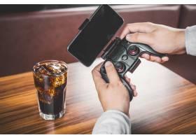 一名男子正在玩他的手机和一个电子游戏控制_969416