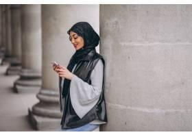 一名穆斯林妇女在外面的街道上使用电话_4410710