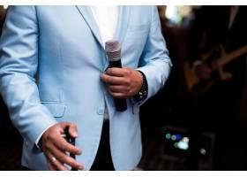 一名身穿蓝色西装的男子手持麦克风_1120603