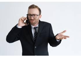 一名身穿黑色夹克的迷茫商人在电话中交谈_4010155