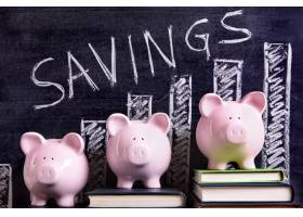 三个粉红色的存钱罐站在一块印有储蓄表的黑_3777231