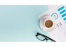 业务预算计划上的咖啡杯和蓝色背景上的眼镜_4743274