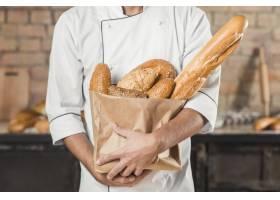 中段男面包师将不同类型的面包装在纸袋里_2966212