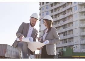 两位建筑师手持蓝图边干边谈项目_5061016