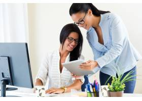 两名女商人在办公室里用数字平板电脑工作_1139272