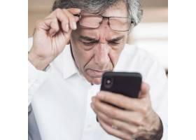 严肃的高级男子看智能手机的特写_3421049