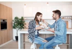 迷人的年轻快乐男女在厨房里吃着早餐早_9629660