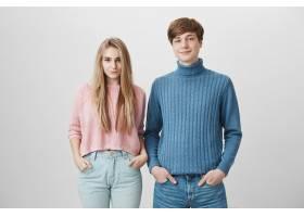 高加索兄妹穿着五颜六色的针织毛衣站在室内_9472875