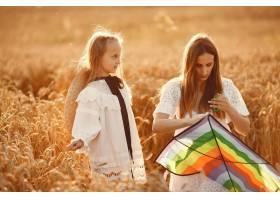 麦田里的一家人穿着白色连衣裙的女人拿_10164599