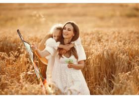 麦田里的一家人穿着白色连衣裙的女人拿_10164602