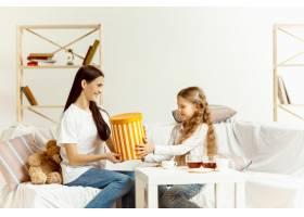小女孩和她迷人的年轻妈妈拿着礼物坐在沙发_10249573