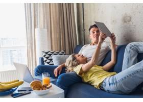 年轻夫妇坐在家里的沙发上看平板电脑在线_9699541