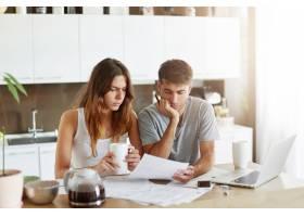 年轻夫妇检查他们的家庭预算_10113395