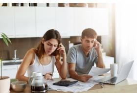 年轻夫妇检查他们的家庭预算_10113401