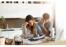 年轻夫妇检查他们的家庭预算_10113422