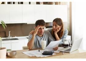 年轻夫妇检查他们的家庭预算_10113439