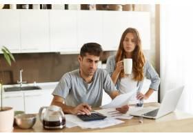 年轻夫妇检查他们的家庭预算_10113445