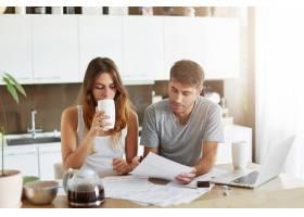 年轻夫妇检查他们的家庭预算_10113739