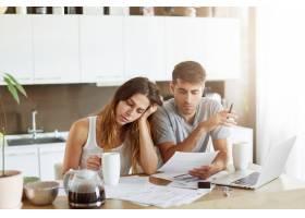 年轻夫妇检查他们的家庭预算_10113741