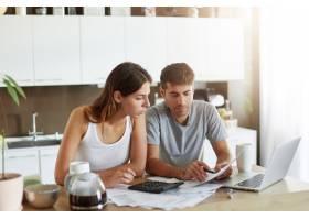 年轻夫妇检查他们的家庭预算_10113750