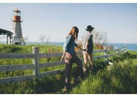 年轻情侣爱着时髦的独立风格走在乡间手牵_10272395