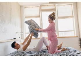 年轻漂亮的夫妇早上在床上玩得很开心独自_9699641