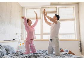 年轻漂亮的夫妇早上在床上玩得很开心独自_9699646