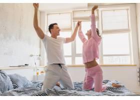 年轻漂亮的夫妇早上在床上玩得很开心独自_9699648