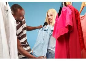年轻漂亮的女孩在商店选购时一边看衣服一边_9708183