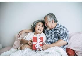 年长的丈夫微笑着在卧室里惊喜地给妻子送礼_4107923