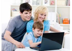 幸福的家庭在家里使用笔记本电脑_10012595