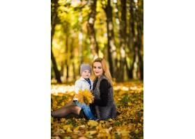 幸福的家庭母亲在秋天的公园里带着孩子玩耍_10121534