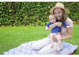 兴高采烈的母亲戴着帽子坐在格子花呢上_9649018