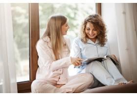 可爱的朋友们穿着睡衣坐在窗台上看杂志的肖_9321027