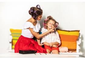 一个小女孩在白色的衣服上玩弄她妈妈的化妆_10250525