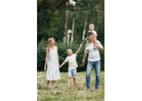 一家人在田野里散步玩玩具飞机_9696058
