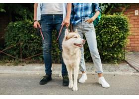 一对年轻时髦的夫妇带着狗在街上散步男人_9699444