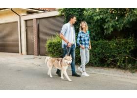一对年轻时髦的夫妇带着狗在街上散步男人_9699446
