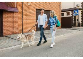 一对年轻时髦的夫妇带着狗在街上散步男人_9699448